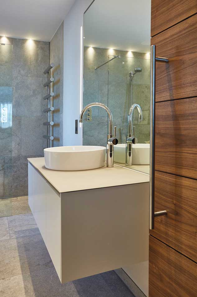 Invoke that boutique-hotel feeling with natural materials and earthy colours. Floating units free up floor space and make smaller en suites feel roomier. Bathroom by JAM Interiors