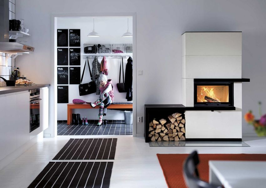 This white cast stone, guillotine-door fireplace has a built-in granite shelf that also serves as a log store. An internal heat tank can be added that acts as an additional thermal store, releasing heat for hours after the stove